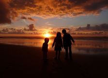 Children at the Beach. On sunset, with storm clouds in the horizon Stock Photo