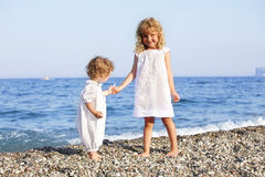 Children on beach. Sisters in white dress royalty free stock photo