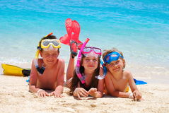 Children on the beach. Children in snorkeling equipment lying on the beach and looking happy Stock Photos