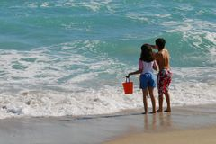 Children at the Beach. A couple of children playing on the shore at the beach Stock Photography