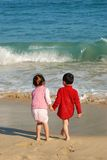 Children in the beach. Young Kids Playing in the surfy beach Royalty Free Stock Image