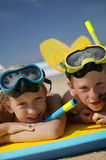 Children at the beach. Boy and girl lying at the beach with swimming equipment Royalty Free Stock Photos