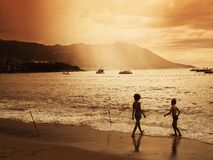 Children on Beach with Boats in Water Stock Photos