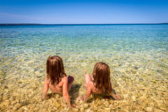 Children on Beach in Croatia island Pag or Hvar. Twins sitting in Turquoise and blue sea water of Adriatic and Mediterranean sea. Beautiful background Stock Image
