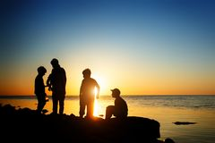 Children on the beach, fishing. Sunset shot, rear view. Sea background. royalty free stock photo