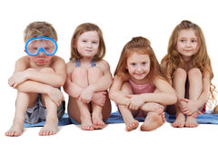 Children in beach suits - boy in diving mask and three girls. Sit on blue big beach towel and draw faces Stock Photo