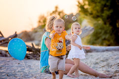 Children on the beach to catch soap bubbles. Children catch soap bubbles and walk on summer beach at sunset Stock Photos