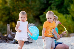 Children on the beach to catch soap bubbles. Children catch soap bubbles and walk on summer beach at sunset Stock Photo