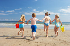 Children on beach vacation. Running towards the ocean stock images