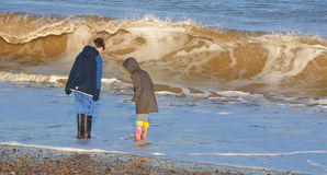 Children on beach in winter and large waves. Royalty Free Stock Photo