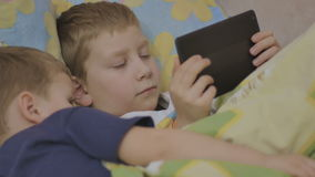 Children on bed with online device. Boys looking at tablet. kids on-line stock video