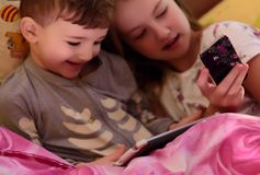 Children in bed playing with gadgets. stock photography