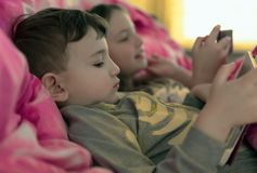 Children in bed playing with gadgets stock photos