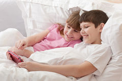 Children in bed playing game console. Close-up. Stock Image