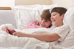 Children in bed playing game console. Close-up. Smiling children are in bed playing a game console. Horizontal Stock Images