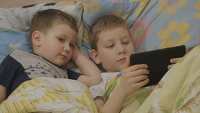 Children in bed use tablet and wave hands. Boys looking at tablet. kids online stock footage