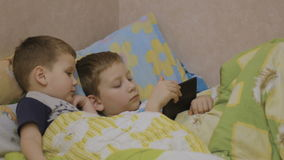 Children in bed watching the show. Boys looking at tablet. kids online stock footage