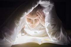 Children bedtime. Brother are reading a book under a blanket with flashlight. Pretty young boy having fun in children room. Children bedtime. Sister and brother Royalty Free Stock Photos