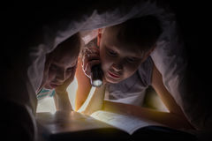 Children bedtime. Sister and brother are reading a book under a blanket with flashlight. Royalty Free Stock Photo
