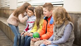 Children on a bench playing Chinese whispers. Modern Children on a bench playing Chinese whispers stock photos