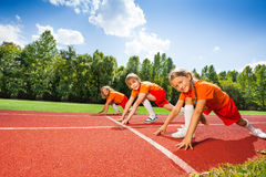Children on bending knees in row ready to run Royalty Free Stock Photography