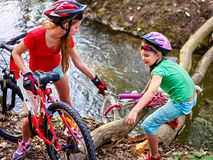Children with bicycle help each other cross river on log. Royalty Free Stock Images