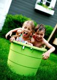 Children in big green bucket. Laughing girl and boy playing in a big green bucket stock images