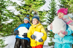 Children with big snowballs in the forest Royalty Free Stock Photo