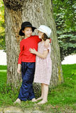 Children By A Big Tree. A boy and girl standing in front of large tree stock photo
