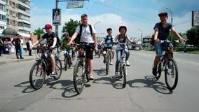 Children on bikes, girls and boys travel column on bike ride around town.