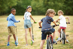 Children with bikes and scooter Royalty Free Stock Images