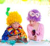 Children birthday party clown wigs blowing cake candles. Children happy birthday party with clown wigs blowing chocolate cake candles stock images