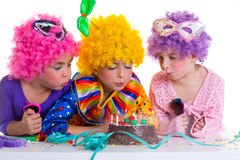 Children birthday party clown wigs blowing cake candles. Children happy birthday party with clown wigs blowing chocolate cake candles royalty free stock photography