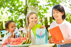 Children on birthday party with gift bags. Kids have fun at a birthday party in the garden with gift bags Stock Photo