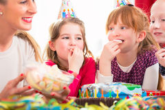 Children on birthday party nibbling candies Stock Image