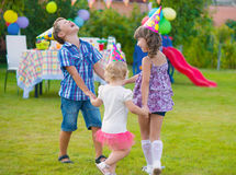 Children birthday party. Three little kids celebrating birthday dancing roundelay Stock Photo