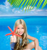 Children blond girl in summer vacation. Tropical beach with starfish Stock Photos