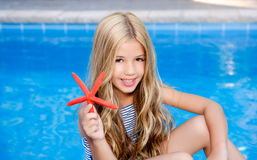 Children blond girl in summer vacation. Children  girl in summer vacation  pool with starfish Royalty Free Stock Images