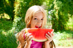 Children blond little girl eating watermelon stock image