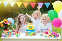 Children blow candles on birthday cake. Kids party. Decoration and food. Boy and girl celebrating birthday of little brother. Transport and car kid event theme stock photos