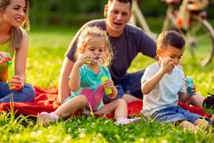 Children blow soap bubbles outdoor- Happy family in the park tog royalty free stock images