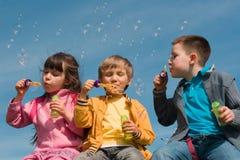 Children blowing bubbles. Children having fun blowing bubbles Royalty Free Stock Image