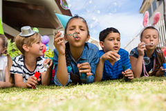 Children blowing bubbles while lying on field Stock Photo