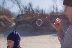 Children blowing bubbles outdoor. Children blowing soap bubbles outdoor in springtime Royalty Free Stock Photo