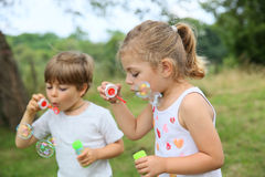 Children blowing bubbles outdoors Stock Photos