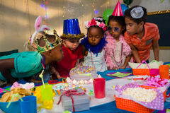 Children blowing candles on cake Stock Photo