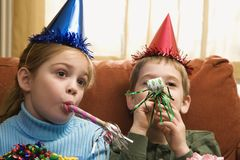 Children blowing noisemakers. stock photography