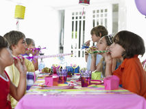 Children Blowing Party Puffers At Table  Stock Images
