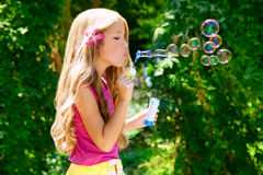 Children blowing soap bubbles in outdoor forest royalty free stock images