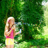 Children blowing soap bubbles in outdoor forest Stock Photos